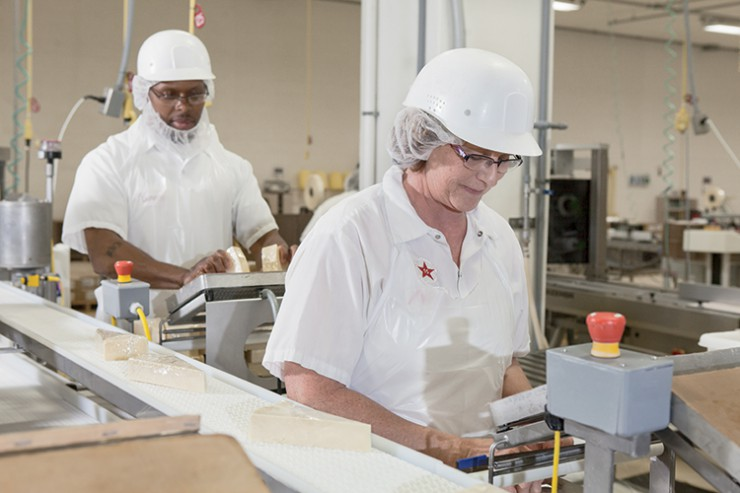 Workers hand wrap and heat seal cheese at the BelGioioso cheese factory